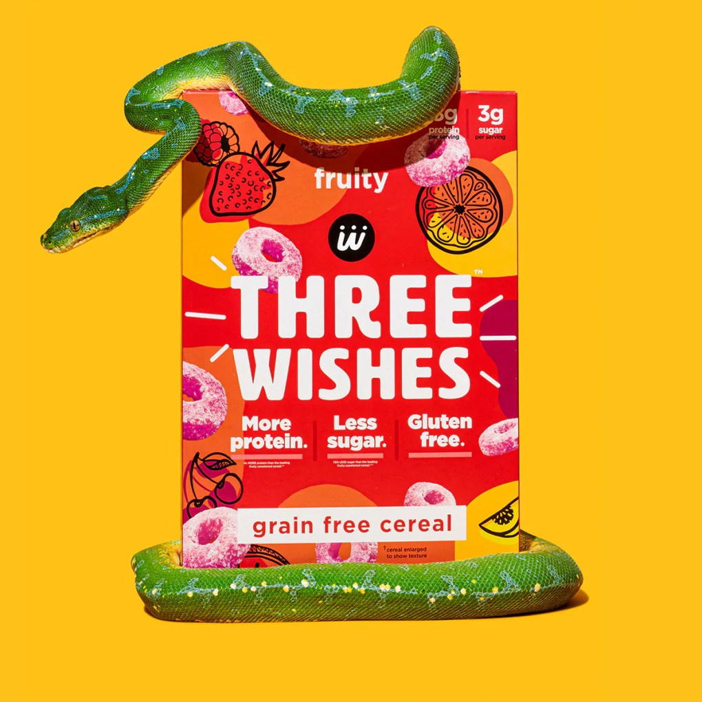 The fruity cereal by Three Wishes Cereal against a yellow background and wrapped by a stuffed animal snake.