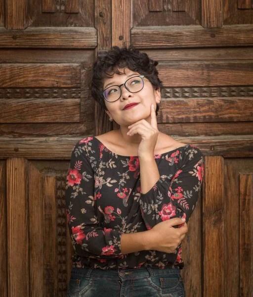 Unsplash-Paola Aguilar-Mujer apoyado contra puerta de madera