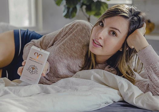 Woman laying on bed holding Promescent female arousal gel.