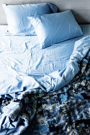 messy blue blanket and two pillows