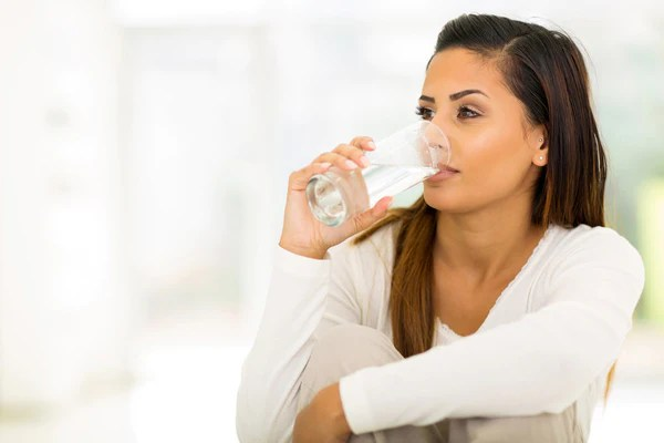 woman wearing white long sleeves drinking a glass of water