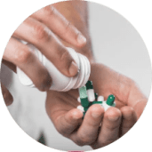 Person pouring pills into hand from a bottle