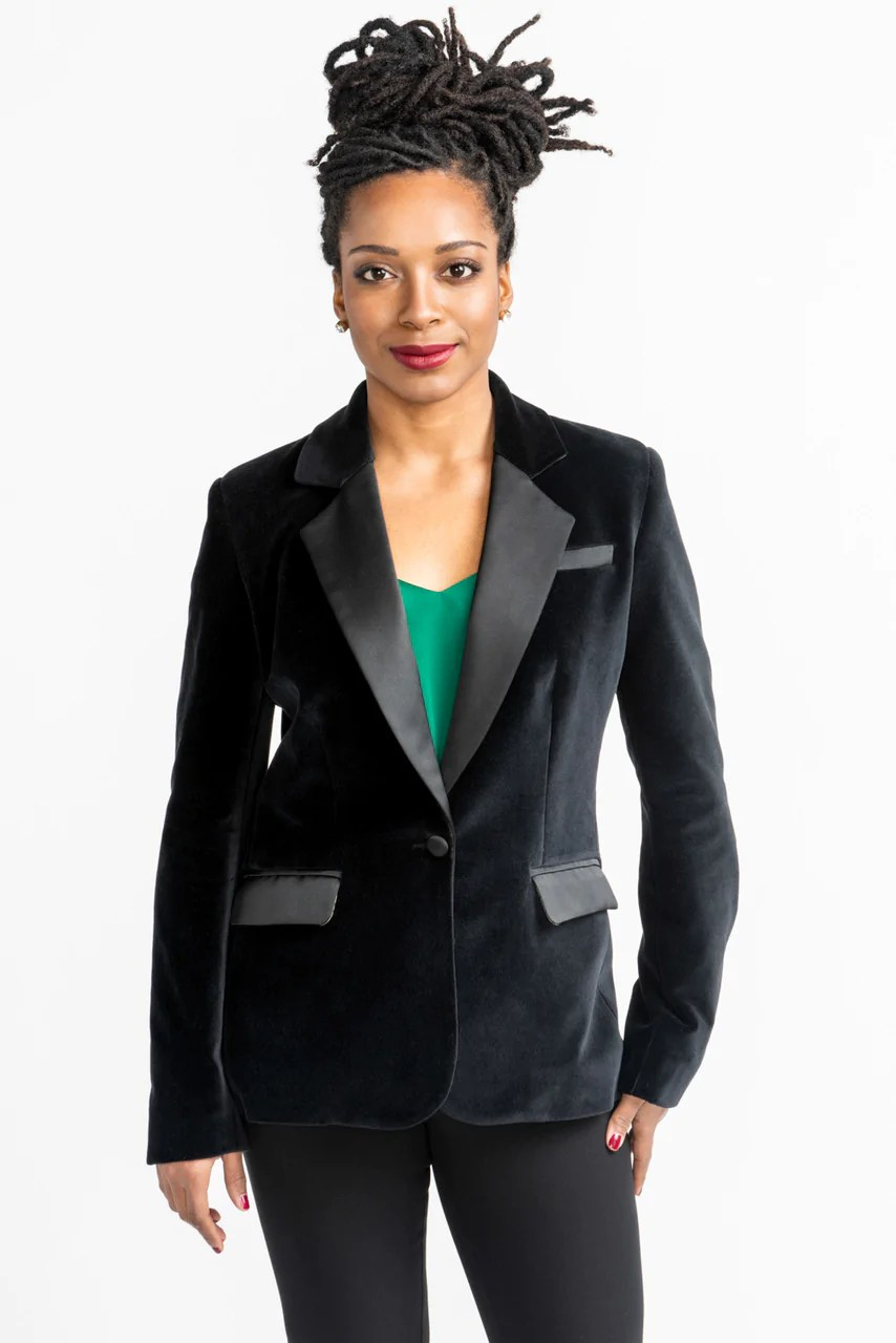 A black woman wearing a tailored blazer that has a velvety look. The blazer has pocket flaps and closes with one button.