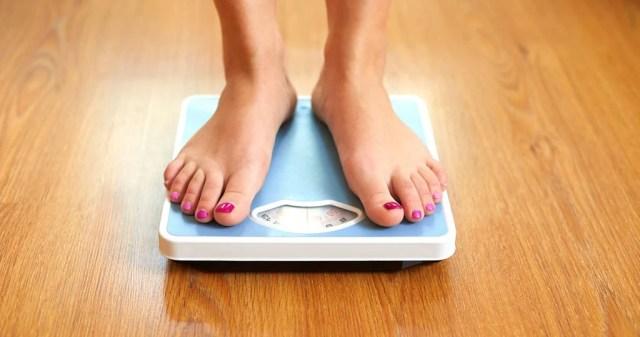 Mujer en las básculas controlando peso