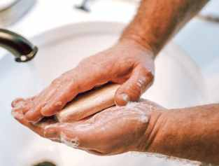 Man washing hands in sink with goat milk soap