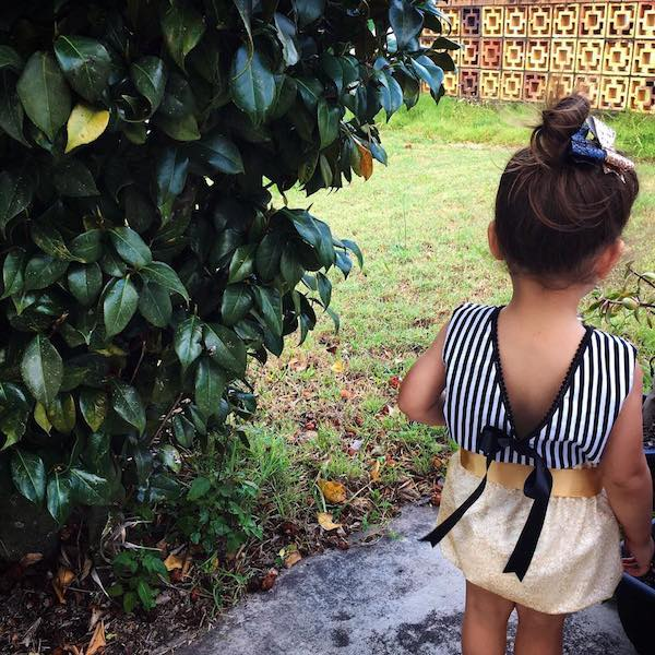 Toddler standing in a garden with her back to the camera. She is wearing Adore Gold Net Lace bloomers by Eighteen Fifty One and a black and white striped top with a V at the back and her hair is up in a bun.