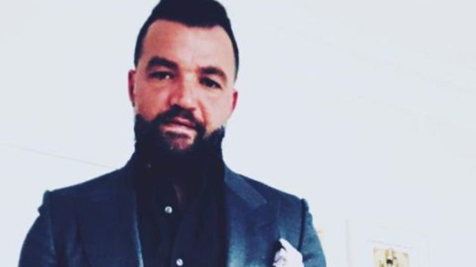 Nick E. Tarabay all suited up in grey coat and black shirt looks at the camera.