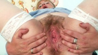 Busty milf in uniform spreads her hairy pussy image