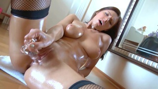 Leggy brunette rubs her pussy in fishnet stockings image