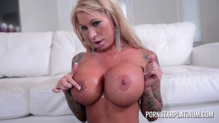 Inked MILF Lolly gets cum on her fake tits image