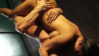 Muscular macho holds Claudia Valentine upside down and eats her pussy image