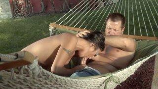 Brunette Kaylani Lei sucks a cock on the hammock image