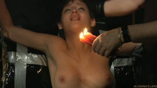 Poor brunette Coco de Mal is suspended and tortured by whip and candle wax image