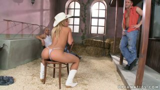 Fabulous cowgirl Nikky Thorne is on her knees sucking two guys image