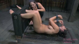 Busty brunette whore Beverly Hills is locked in_the leg pillory image