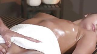 Oiled babe wanks and fucks masseur till cumshot image
