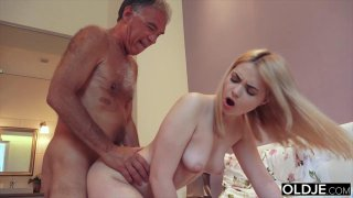 Nympho_sucks_grandpa_cock_has_sex_with_him_on_her image