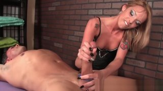 Inked femdom masseuse tugging on roped cock image