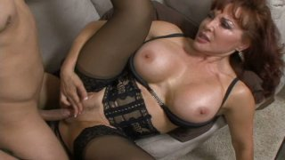 Busty redhead milf is dressed in sexy lingerie and stockings image
