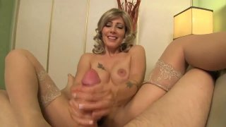 Busty MILF in stockings gives an amazing handjob in POV image