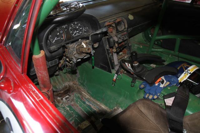 """""""The Office"""" in the author's Spec Miata. It is a completely Stripped interior, save the gauge cluster. A full roll cage, fire extinguisher, removable steering wheel and window and interior nets are pretty much it. Photo Evan D'Amico"""