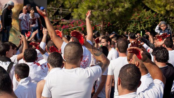 Men chant 'Ya Hussein' as they beat their heads. Image by James Haines-Young