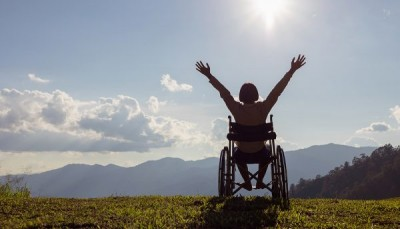 Person on a wheelchair with his arms up in the air photograph taken from behind