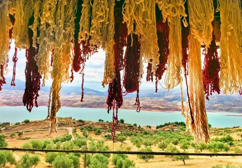 La laine teinte sèche au vent et au soleil sur la véranda de Mustafa qui surplombe les montagnes et le lac du Haut Atlas.