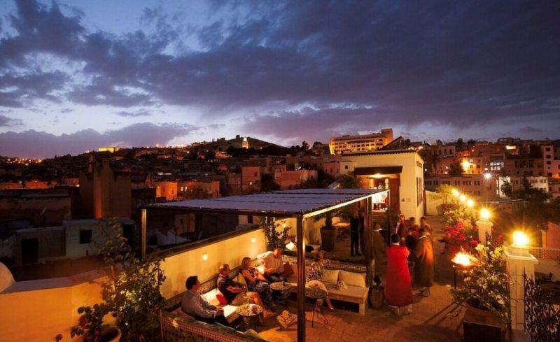 Des lumières chaudes et des musiciens en manteau rouge semblent destinés à compléter le ciel violet au-dessus. Photo Palais Amani