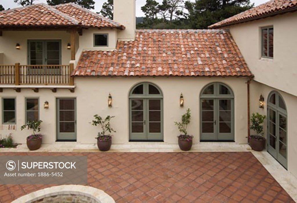 exterior of a spanish style luxury home with stucco walls a red tile roof and mexican tile patio stock photo 1886 5452 superstock