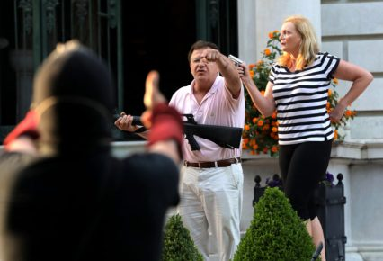 Armed homeowners standing in front of their house along Portland Place confront protesters as they march to Mayor Lyda Krewson's house on Sunday, June 28, 2020, in the Central West End in St. Louis. (Laurie Skrivan/St. Louis Post-Dispatch/TNS)