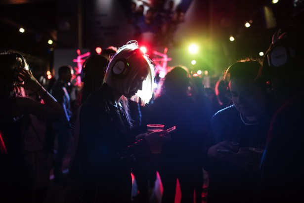 A woman looks at her phone as she takes part in a silent disco.
