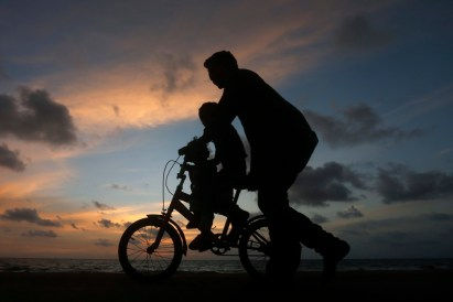 A man guides a child riding a two-wheel bike. It's sunset, and the figures appear as silhouettes.
