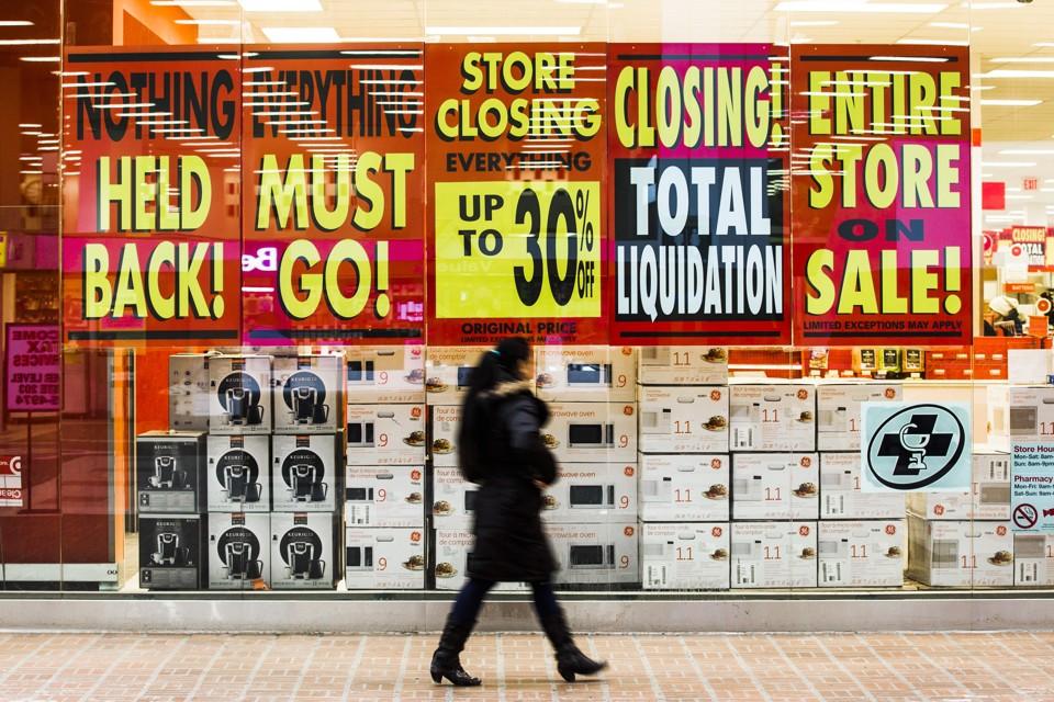Uma loja de varejo com placas que anunciam uma venda de liquidação pré-encerramento