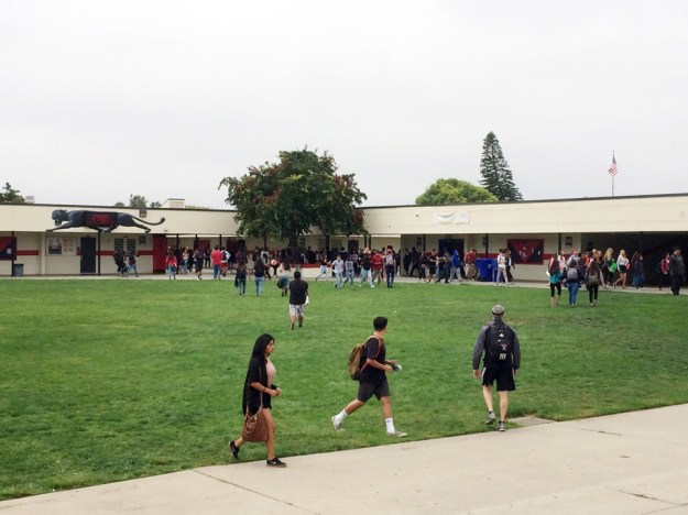 Students walk across a grassy field in front of a school building.