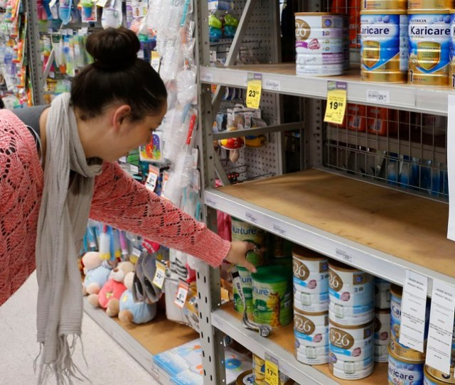 A Woman Browses For Milk Powder At A Stand With A Food Recall Notice From Nutricia In A Supermarket In Huntly Waikato Region In New Zealand August