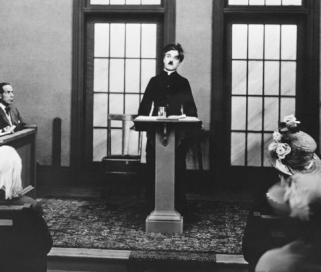 A Black And White Photo Of Charlie Chaplin At A Podium Surrounded By