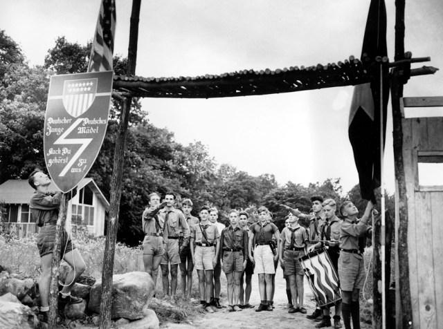 21 lipca 1937, New Jersey. Młodzież amerykańskich nazistów stoi na baczność, ponieważ flaga amerykańska i flaga ich organizacji są opuszczane podczas ceremonii o zachodzie słońca.