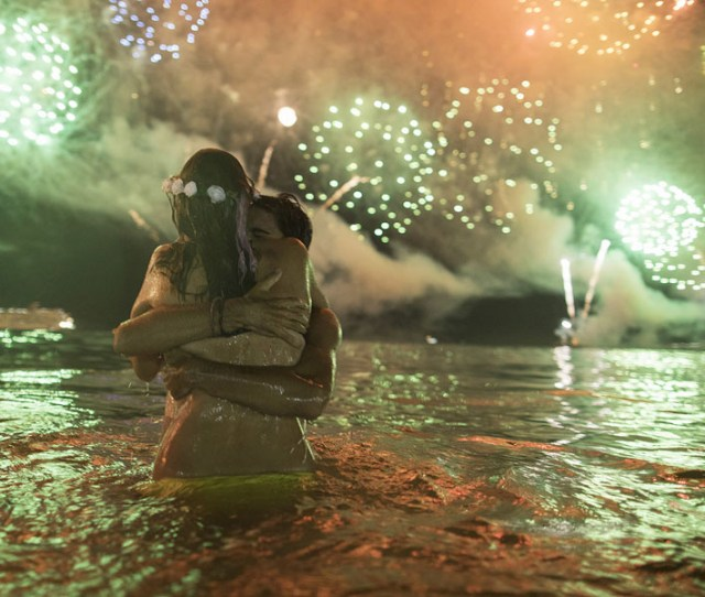 A Couple Hug Each Other As They Watch Fireworks Exploding Over Copacabana Beach During New Years Celebrations In Rio De Janeiro Brazil On January 1