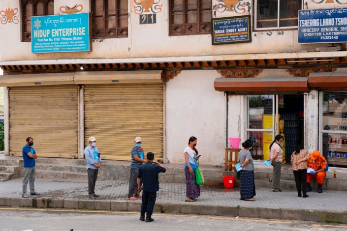 Local residents maintain social distancing as they stand in a queue to buy groceries outside a store during a nationwide lockdown imposed as a preventive measure against the spread of the COVID-19 coronavirus at Thimphu in Bhutan, on August 20, 2020.