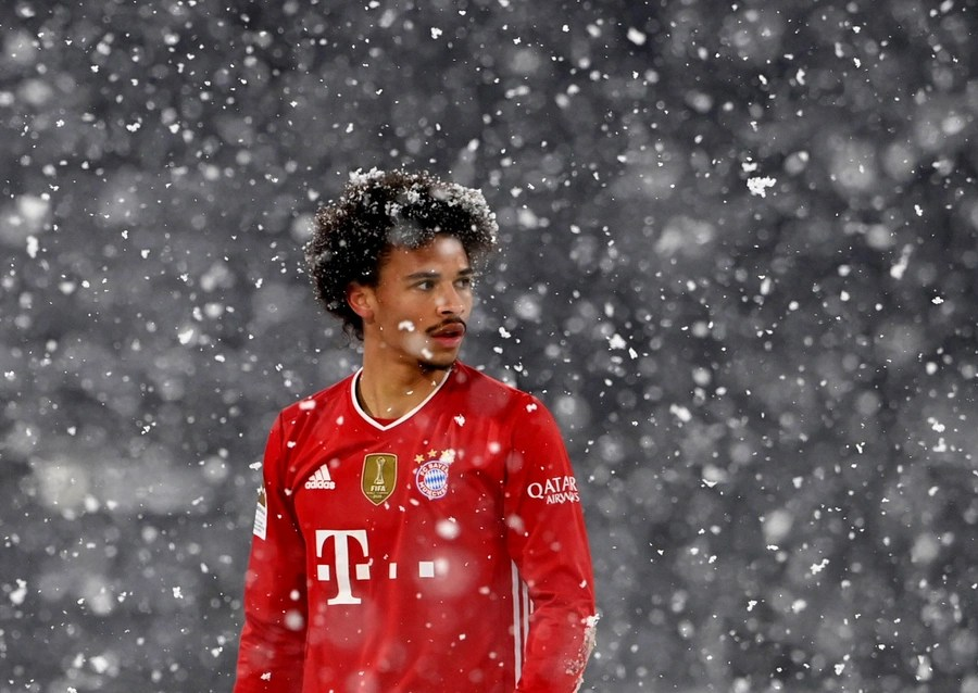 A soccer player stands amid falling snowflakes.
