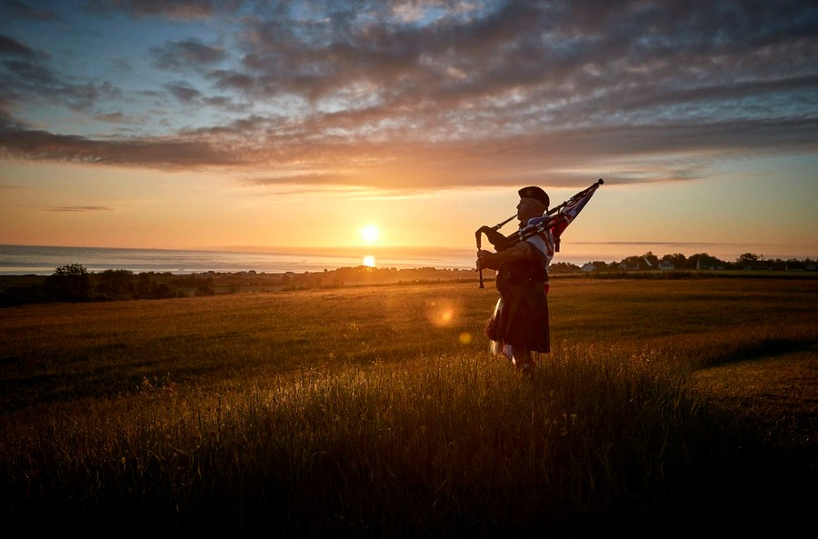 A man stands in a field playing the bagpipes at sunrise.