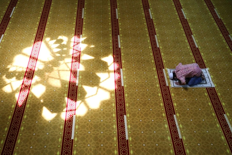 A man prays inside a large space inside a mosque.