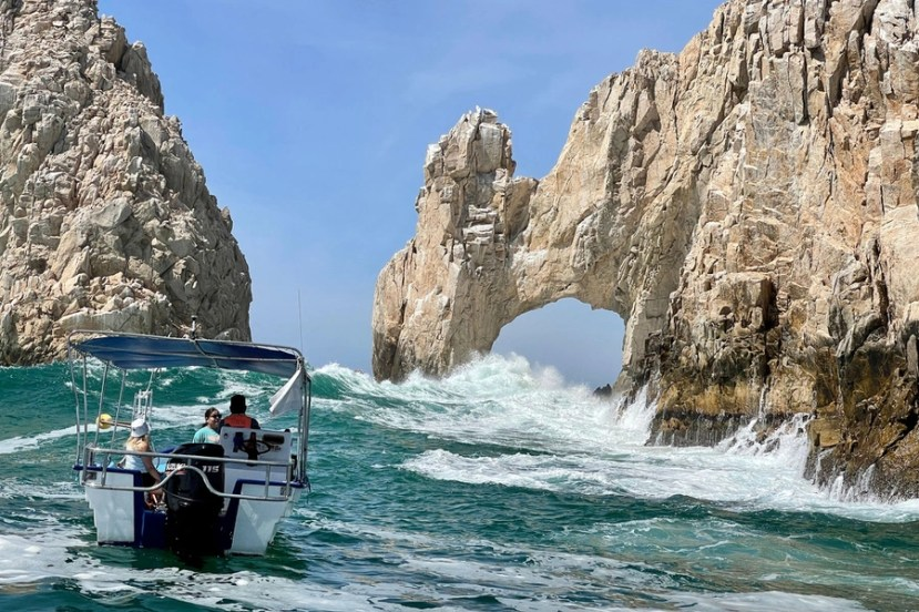 Tourists ride in a boat near waves crashing against a natural arch formation in rocks.