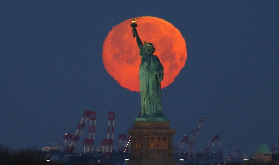 The moon is seen behind the Statue of Liberty.