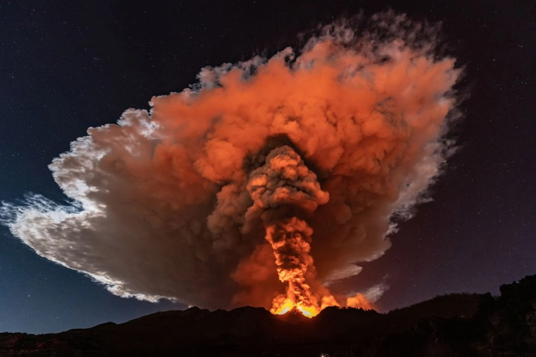 Reddish light from lava illuminates the base of a column of ash rising into a cloud above a volcano.