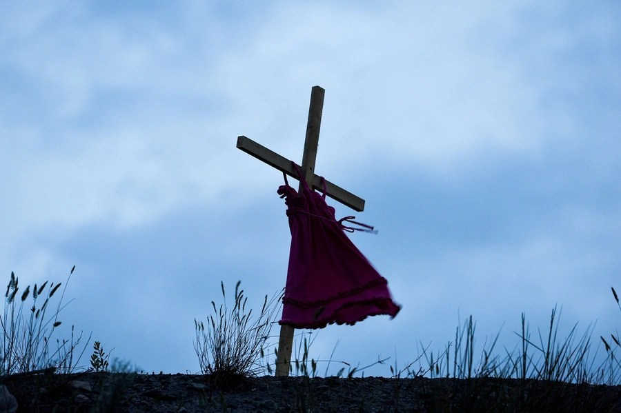 A small red dress hangs from a wooden cross.