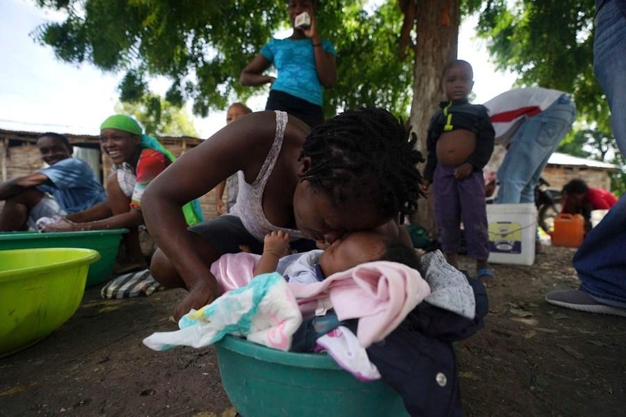 Una donna si strofina il naso con il nipotino neonato, tra gli altri, rifugiandosi nel cortile di una scuola.