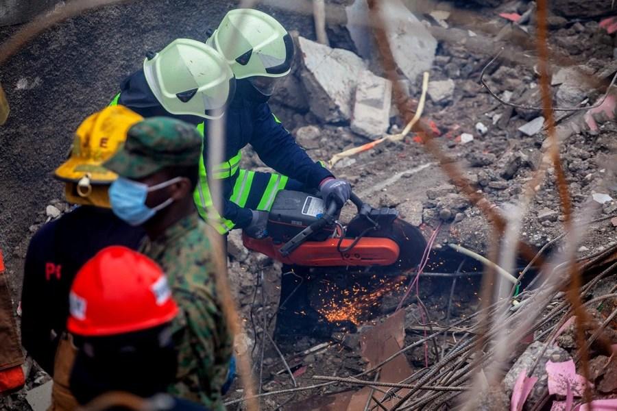 I vigili del fuoco utilizzano strumenti per tagliare cumuli di macerie.