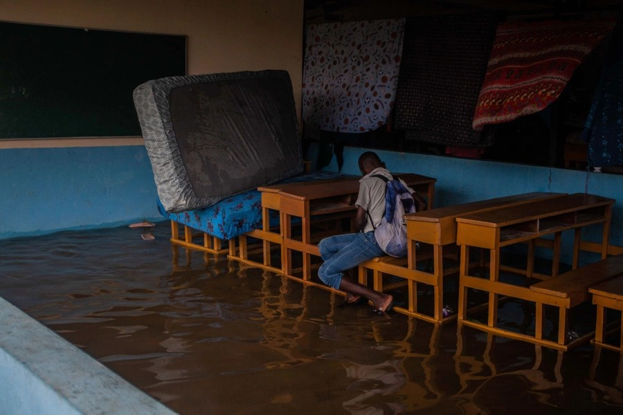 Un bambino siede su una panchina in un'aula buia allagata.